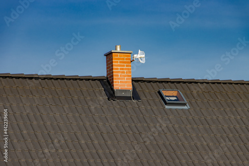 Canvas Roof of the house with a chimney and WiFi antenna, on a background of blue sky