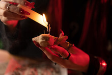 Melted Wax From A Candle Falls On A Voodoo Doll In The Hands Of A Witch Close Up.