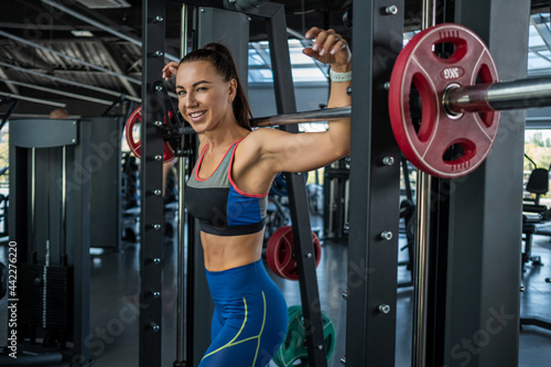 Foto Cheerful fit young brunette standing near Smith machine at gym