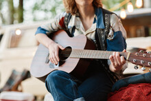 Close-up Of Young Woman Sitting On The Nature And Playing Guitar