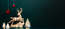 Christmas Gold Reindeer With Xmas Tree Lamp Lights With Red Baubles Hanging On Dark Blue Green Background.banner Mockup For Display Of Design Or Invitation Card For Holiday Event