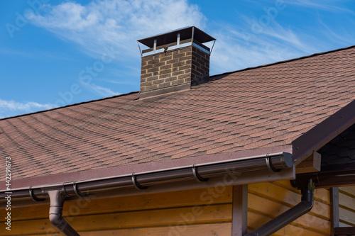 Foto Bitumen asphalt roofing shingles and brick chimney pipe on a wooden house