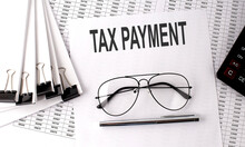TAX PAYMENT Text On Paper With Chart And Office Tools , Business Concept