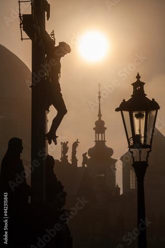 Billede på lærred Prague - The cross on the charles bridge by sunrise - silhouette