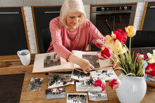 A Concentrated Elderly Woman Looking At Old Photos In Album In Kitchen