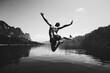 Leinwandbild Motiv Man jumping with joy by a lake