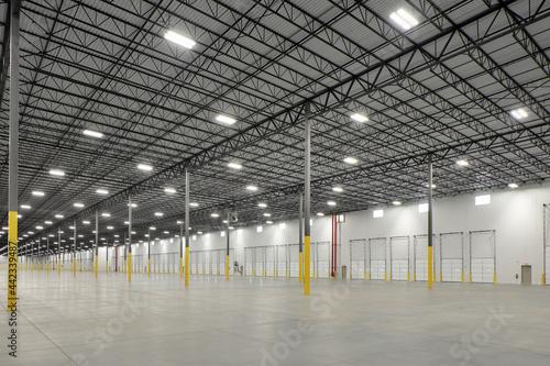 Billede på lærred Interior of empty lit storage warehouse industrial facility building