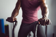 Midsection Of African American Man Exercising At Gym Using Rowing Machine