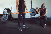 Diverse Fitness Trainer And Man Exercising At Gym, Lifting Weights On Barbell And Advising