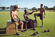 Diverse Group Of Happy Shirtless Men Exercising Outdoors, Taking A Break Talking And Bumping Fists