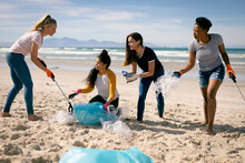 Diverse Group Of Female Friends Picking Up Rubbish From Beach