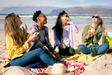 Happy Group Of Diverse Female Friends Having Fun, Siting On The Beach And Eating
