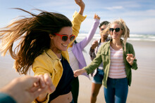 Happy Group Of Diverse Female Friends Having Fun, Walking Along Beach Holding Hands And Laughing