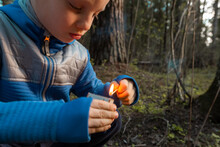Child Lighting Match. The Fire In The Hands Of A Children. A Little Boy Plays With Flame. Danger Of Woodfire
