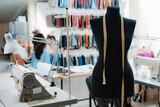 Fototapeta Kawa jest smaczna - studio mannequin dummystylish fashionable trendy clothes on hangers, dressmaking workplace, tailor shop, sewing workshop