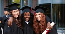 Happy Group Of Mature Students On Graduation Day Embracing With Each Other. Three Best Girl Friends In Academic Gowns And Caps Hugging In Front Of The Camera