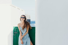 Relaxed Woman In Summer Dress Standing Near House Gate At Seaside