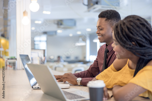 Foto african college university students using laptop together .