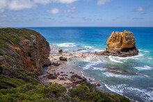 View From Above On A Large Rocky Reef Of Large Ocean Waves. Blue Panorama On A Beautiful Steer Rocky Shore, Sandy Beaches And A Huge Brown Rock Protruding From The Water. Australia. Great Ocean Road.