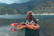 Girl Canoeing On A Lake In The Mountains On A Cloudy Day. Moody Atmosphere On Lake Gizhgit In The Village Of Bylym, Kabardino-Balkaria