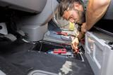 Fototapeta Miasto - Man working on the starter battery of a van