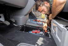 Man Working On The Starter Battery Of A Van
