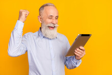 Photo Of Happy Old Cheerful Man Raise Fist Winner Hold Tablet Celebrate Isolated On Shine Yellow Color Background