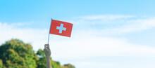 Hand Holding Switzerland Flag On Blue Sky Background. Switzerland National Day And Happy Celebration Concepts