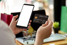 Woman Holding Smart Phone And Credit Card For Shopping Online.Blank Screen Monitor For Graphic Display Montage.
