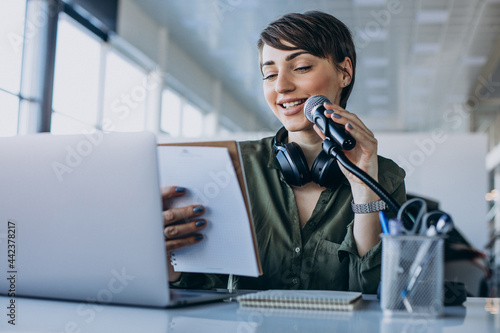 Young woman with microphone recording voice acting Fototapet