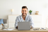Successful freelancer. Happy man sitting at workplace with laptop computer, smiling and looking at camera
