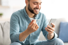 Happy Young Man Holding Toy Plane And Using Smartphone To Book Vacation Or Buy Tickets Online From Home, Selective Focus