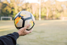 Close Up Shot Of A Man Holding A Soccer Ball In The Field With A Blurry Background