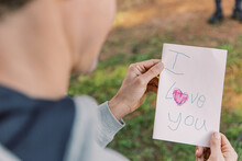 A Letter With An I Love You Text And A Red Heart Written On A Small Paper Held By A Man In Blur
