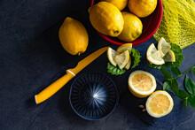 Vista Superior Con Espacio De Copia . Limones Frescos Y Maduros. Fondo De Alimentos Saludables. Elegante Diseño De Fondo De Los Limones Y Rodajas De Limón Con Exprimidor Y Cuchillo En El Cemento Oscur
