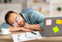 Lazy Unproductive Young Guy Wearing Funny Sticky Notes With Open Eyes On His Glasses, Sleeping At Workplace