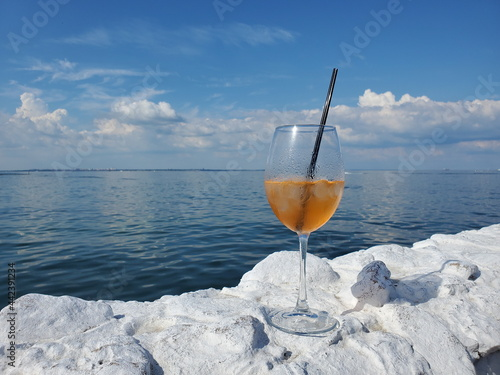 Foto Wine glass of luxury cocktail Aperol Spritz on white stones with amazing ocean view and cloudscape