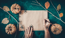 Halloween Grunge Dark Green Background, Pumpkins, Black Spiders, Dry Branches, Orange Leaves Decoration. Autumn Composition Frame, Flat Lay, Vintage Paper, Woman Hand With Pencil, Copy Space.