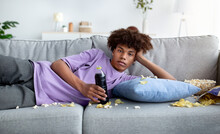 Bored Black Teenager Lying On Couch With Scattered Food, Watching Dull Show Or Movie On TV, Killing Time At Home