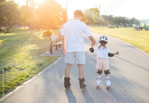 Billede på lærred Father and little girl skating in park. Active day.