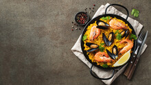 Traditional Spanish Seafood Paella In Pan With Chickpeas, Shrimps, Mussels, Squid On Brown Concrete Background. Top View With Copy Space