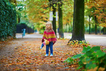 Adorable Toddler Girl Walking In Park On A Fall Day In Paris, France