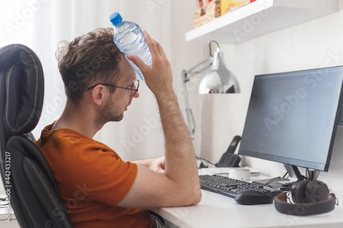 Murais de parede Working at home man suffering from heat and thirst cools down with water bottle