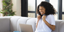 Excited Young Female With Curly Hair And Laptop Sitting At Home On The Couch Received An Email With Great News
