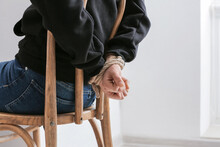 Female Hostage With Tied Hands Sitting On Chair In Room