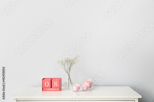 Fototapeta Candles with cube calendar and vase on shelf near light wall