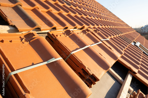 Canvastavla Stacks of yellow ceramic roofing tiles for covering residential building roof under construction