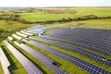 Aerial View Of Solar Power Plant Under Construction On Green Field. Assembling Of Electric Panels For Producing Clean Ecologic Energy.