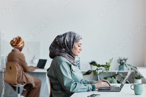 Fotografija Side view portrait of modern Middle-Eastern woman wearing headscarf in office an