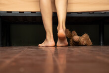 Feet Near The Bed On The Wooden Floor Of The House And Under The Bed Lies A Teddy Bear, Home , Feet On The Floor